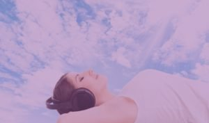 A woman imagines herself in the clouds with sound meditations through her sound-cancelling headphones.